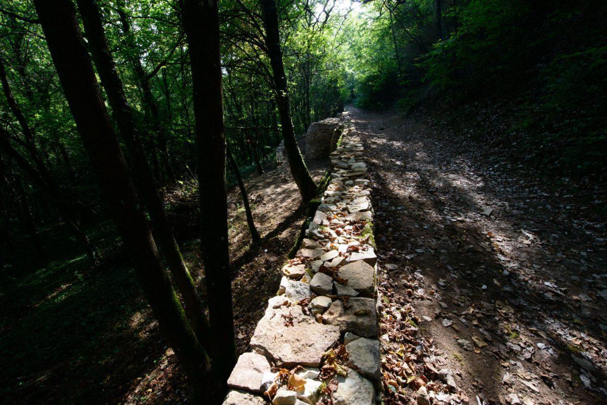Le chemin des Pierres Blanches, avec visible en arrière plan la caborne adossée au mur de soutènement du chemin.